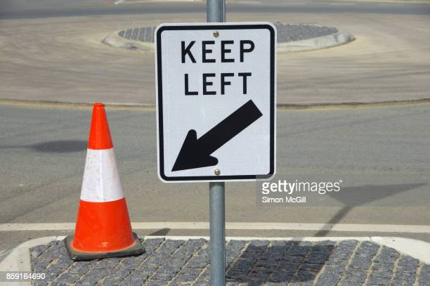 'Keep Left' traffic sign and a traffic cone on a traffic circle in Canberra, Australian Capital Territory, Australia