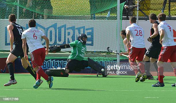 Keeper Devon Manchester of New Zealand deflects a ball from Ben Arnold of England during their match at the men's Hockey Champions Trophy tournament...