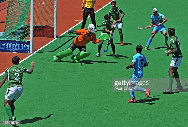 Keeper Imran Butt of Pakistan deflects the ball in front of goal during the bronze medal match against India at the men's Hockey Champions Trophy...