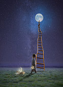Far, far, away, out on a grassy field under a night sky, a little girl is holding a star she pulled from her box full of moon and stars.  She is about to climb up a rickety ladder, that reaches all th