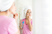 Woman looking at herself in mirror while applying essential oil with cotton pad