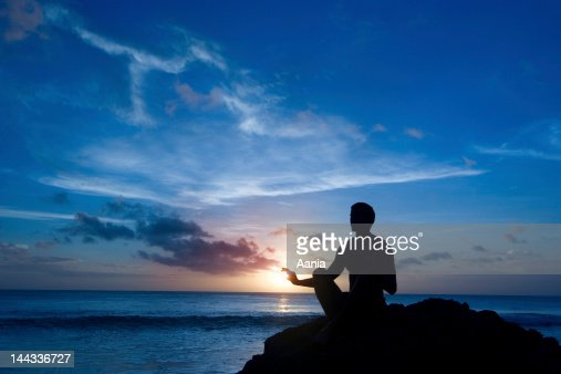 Keeping sun - young man meditating on the beach : Stock Photo
