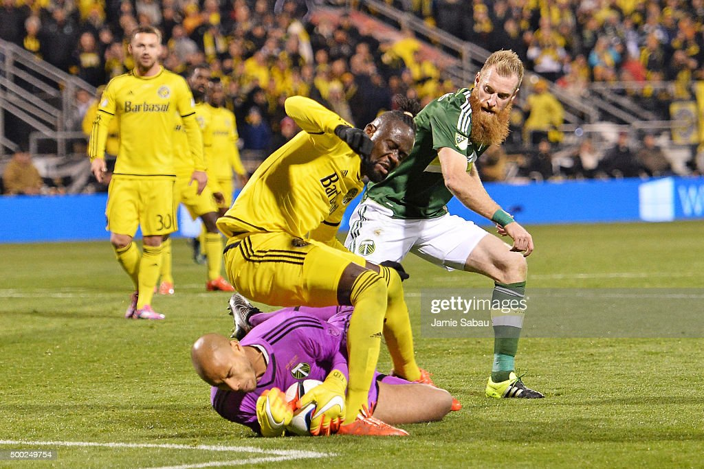 Kei Kamara #23 of the Columbus Crew SC falls over goalkeeper Adam Kwarasey #12 of the Portland Timbers as Nat Borchers #7 of the Portland Timbers defends in the second half on December 6, 2015 at MAPFRE Stadium in Columbus, Ohio. Portland defeated Columbus Crew SC 2-1 to claim the MLS Cup title.