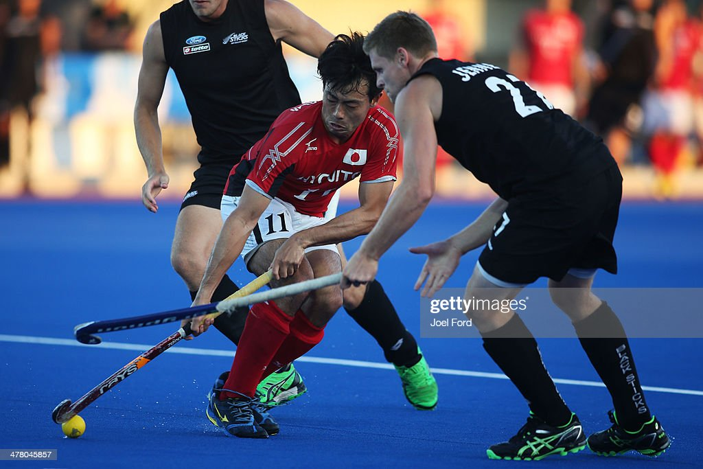 Kei Kawakami of Japan and Stephen Jenness of New Zealand fight for the ball during the Test Match between the New Zealand Black Sticks and Japan at Blake Park on March 12, 2014 in Mount Maunganui, New Zealand.