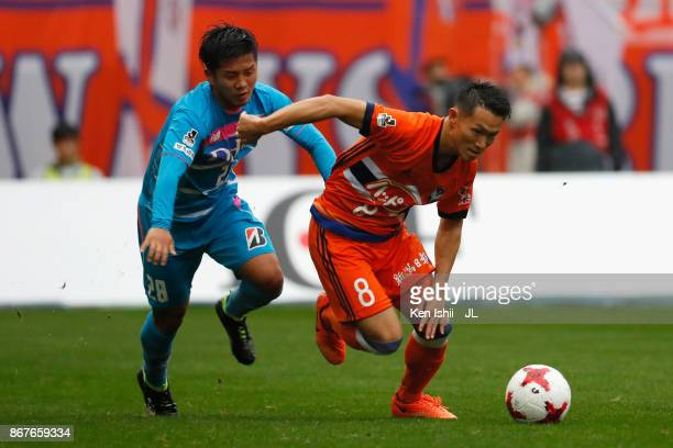 Kei Koizumi of Albirex Niigata and Hiroto Ishikawa of Sagan Tosu compete for the ball during the JLeague J1 match between Albirex Niigata and Sagan...