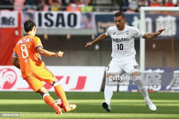 Kei Koizumi of Albirex Niigata and Lukas Podolski of Vissel Kobe compete for the ball during the JLeague J1 match between Albirex Niigata and Vissel...