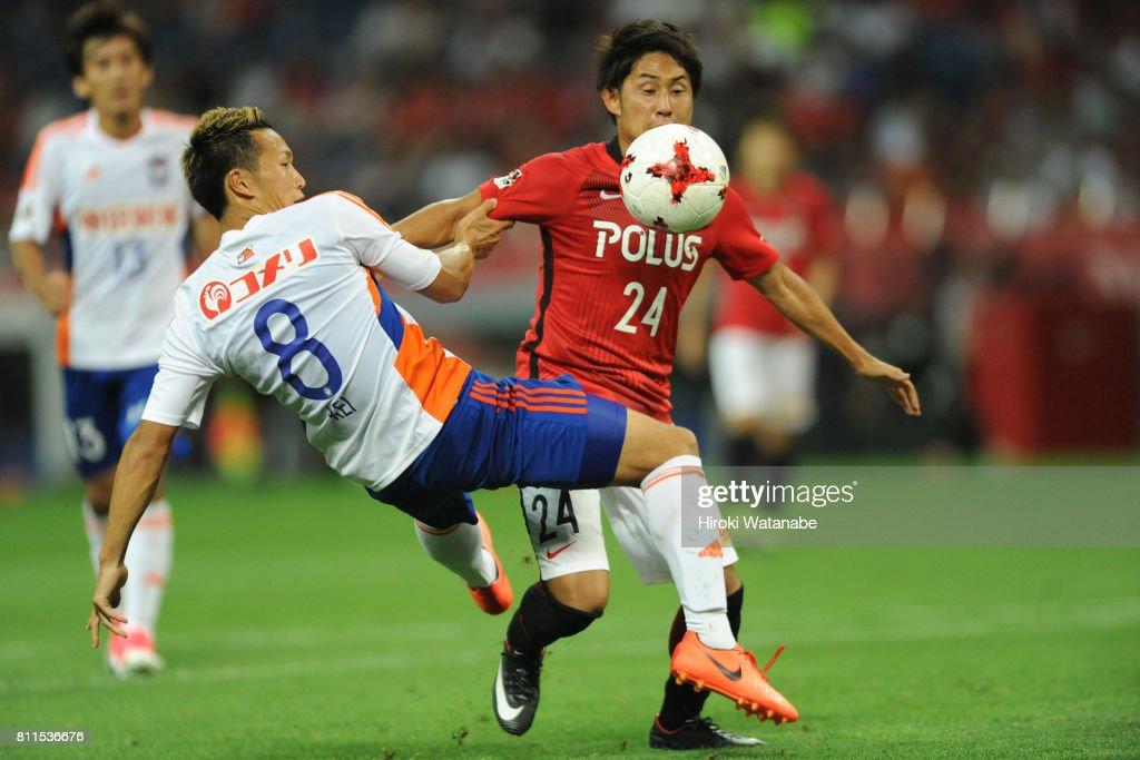 Kei Koizumi #8 of Albirex Niigata and Takahiro Sekine #24 of Urawa Red Diamonds compete for the ball during the J.League J1 match between Urawa Red Diamonds and Albirex Niigata at Saitama Stadium on July 9, 2017 in Saitama, Japan.
