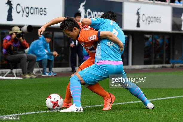 Kei Koizumi of Albirex Niigata controls the ball under pressure of Masato Fujita of Sagan Tosu during the JLeague J1 match between Sagan Tosu and...