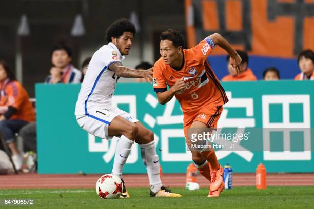 Kei Koizumi of Albirex Niigata goes past Leandro of Kashima Antlers during the JLeague J1 match between Albirex Niigata and Kashima Antlers at Denka...