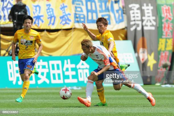 Kei Koizumi of Albirex Niigata is challenged by Hiroaki Okuno of Vegalta Sendai during the JLeague J1 match between Vegalta Sendai and Albirex...