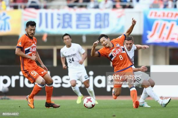 Kei Koizumi of Albirex Niigata is challenged by Lukas Podolski of Vissel Kobe during the JLeague J1 match between Albirex Niigata and Vissel Kobe at...