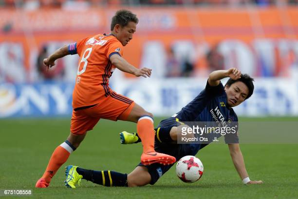 Kei Koizumi of Albirex Niigata is tackled by Shinnosuke Nakatani of Kashiwa Reysol during the JLeague J1 match between Albirex Niigata and Kashiwa...