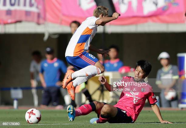 Kei Koizumi of Albirex Niigata is tackled by Yasuki Kimoto of Cerezo Osaka during the JLeague J1 match between Cerezo Osaka and Albirex Niigata at...