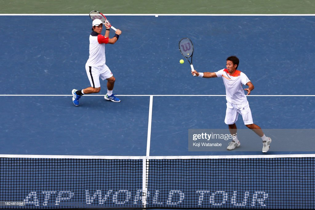 Kei Nishikori of Japan (L) and Yasutaka Uchiyama of Japan in action during the men's first round doubles match against Ivan Dodig of Czech Republic and Marcelo Melo of Brazil during day one of the Rakuten Open at Ariake Colosseum on September 30, 2013 in Tokyo, Japan.
