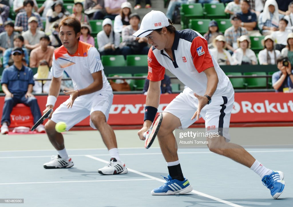 Kei Nishikori of Japan (R) and Yasutaka Uchiyama of Japan in action during the men's first round doubles match against Ivan Dodig of Czech Republic and Marcelo Melo of Brazil during day one of the Rakuten Open at Ariake Colosseum on September 30, 2013 in Tokyo, Japan.