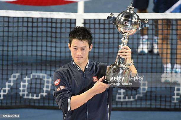 Kei Nishikori of Japan celebrates with his trophy after the men's singles final match against Milos Raonic of Canada on day seven of Rakuten Open...