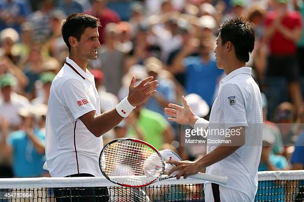 Kei Nishikori of Japan greats Novak Djokovic of Serbia after their men's singles semifinal match on Day Thirteen of the 2014 US Open at the USTA...