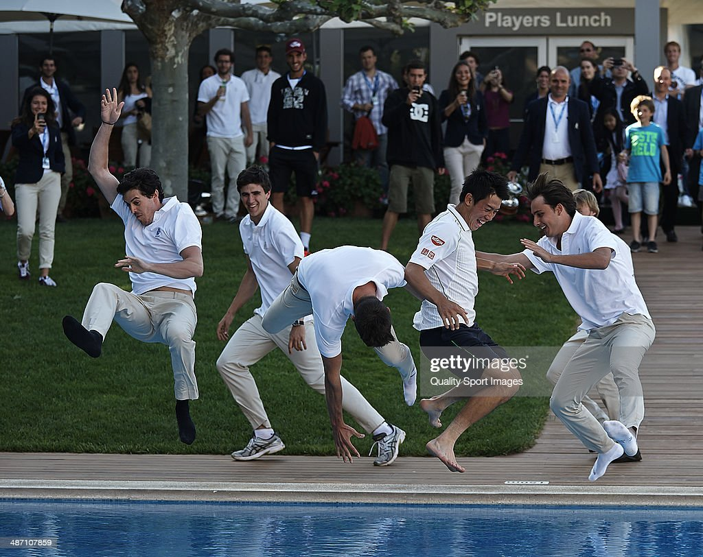 Kei Nishikori (2nd R) of Japan is thrown into the pool after his victory against Santiago Giraldo of Colombia after day eight of the ATP Barcelona Open Banc Sabadell at the Real Club de Tenis Barcelona on April 27, 2014 in Barcelona, Spain.