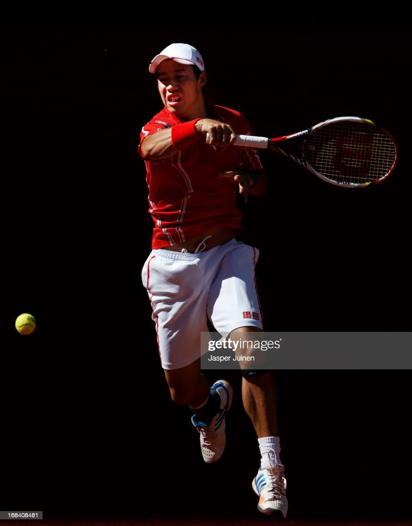 Kei Nishikori of Japan jumps to play a forehand to Roger Federer of Switzerland on day six of the Mutua Madrid Open tennis tournament at the Caja Magica on May 9, 2013 in Madrid, Spain.