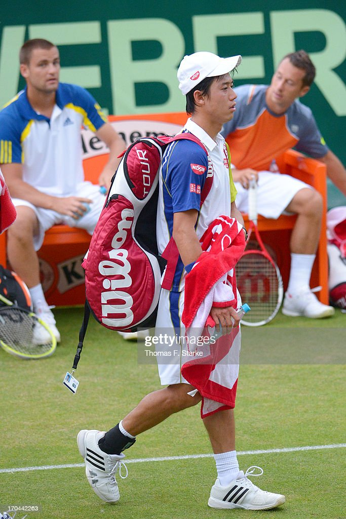 Kei Nishikori of Japan leaves the court after loosing his doubles match with Milos Raonic of Canada against Philipp Kohlschreiber (BACK R) of Germany and Mikhail Youzhny (BACK L) of Russia during day four of the Gerry Weber Open at Gerry Weber Stadium on June 13, 2013 in Halle, Germany.
