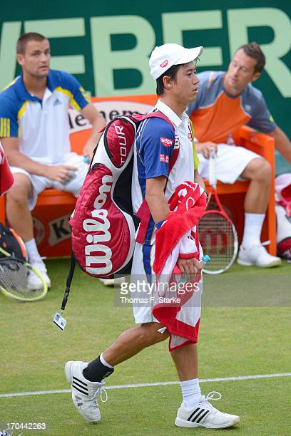 Kei Nishikori of Japan leaves the court after loosing his doubles match with Milos Raonic of Canada against Philipp Kohlschreiber of Germany and...