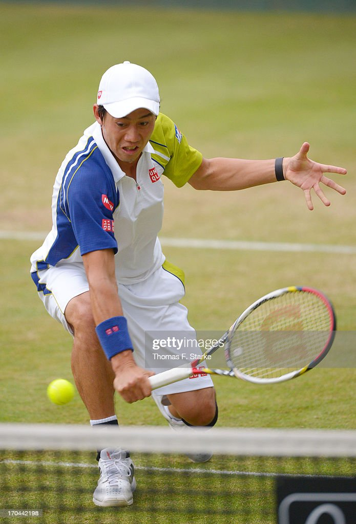 Kei Nishikori of Japan play a backhand in his doubles match with Milos Raonic of Canada against Philipp Kohlschreiber of Germany and Mikhail Youzhny of Russia during day four of the Gerry Weber Open at Gerry Weber Stadium on June 13, 2013 in Halle, Germany.