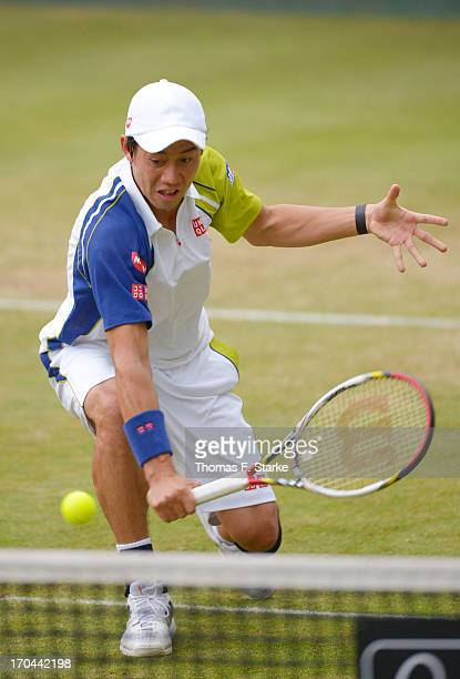 Kei Nishikori of Japan play a backhand in his doubles match with Milos Raonic of Canada against Philipp Kohlschreiber of Germany and Mikhail Youzhny...