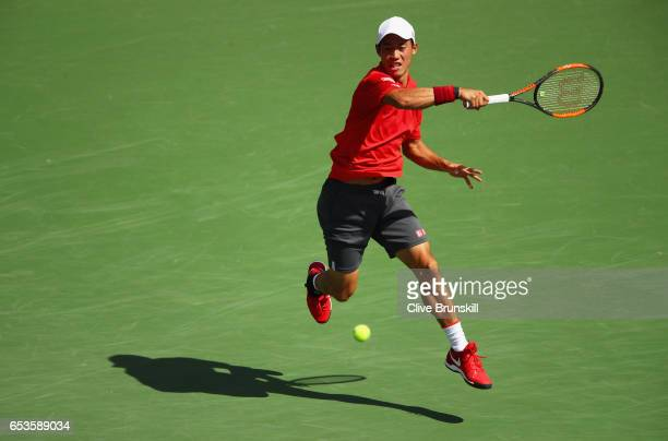 Kei Nishikori of Japan plays a forehand against Donald Young of the United States in their fourth round match during day ten of the BNP Paribas Open...