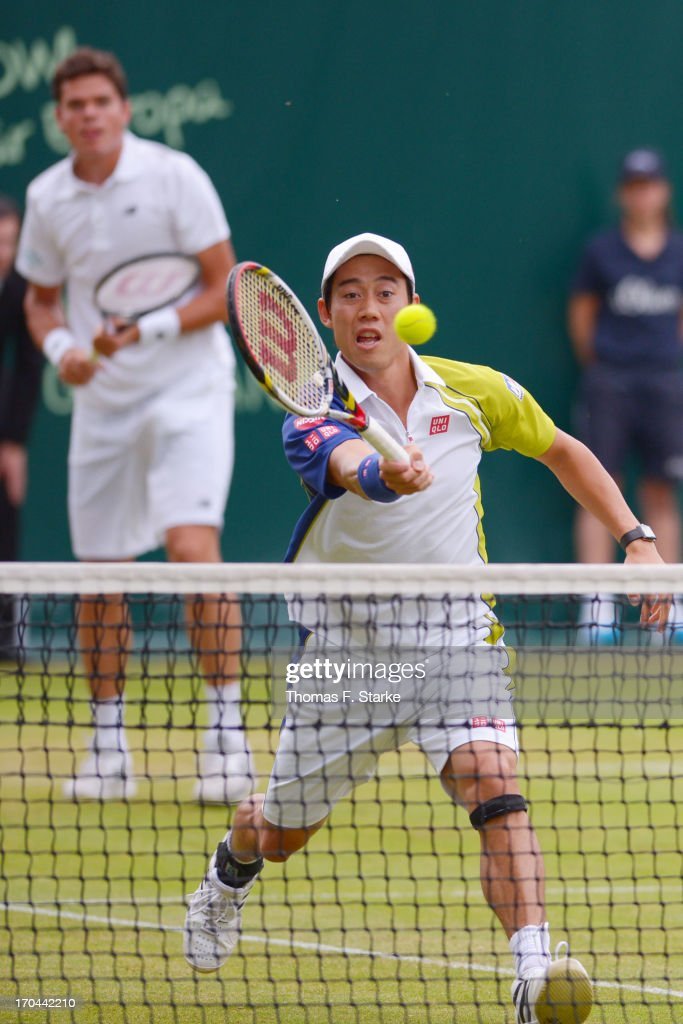 Kei Nishikori (FRONT) of Japan plays a forehand in his doubles match with Milos Raonic of Canada against Philipp Kohlschreiber of Germany and Mikhail Youzhny of Russia during day four of the Gerry Weber Open at Gerry Weber Stadium on June 13, 2013 in Halle, Germany.