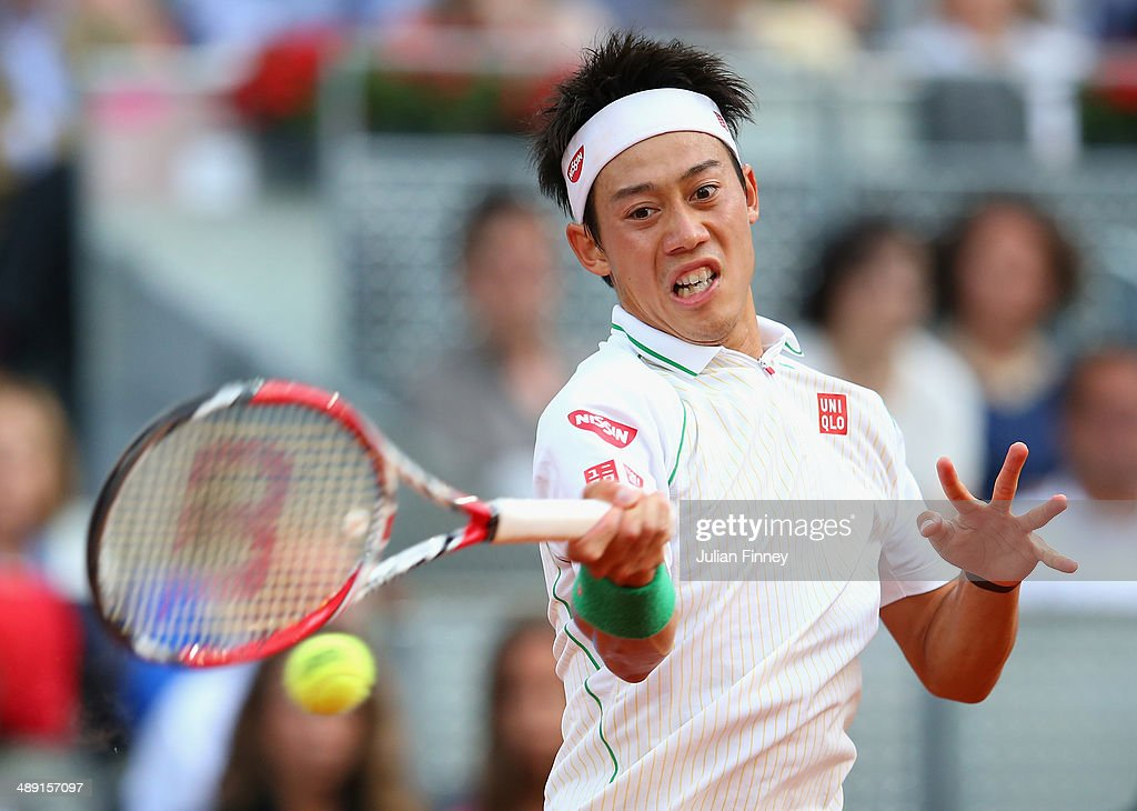 Kei Nishikori of Japan plays a forehand in his match against David Ferrer of Spain during day eight of the Mutua Madrid Open tennis tournament at the Caja Magica on May 10, 2014 in Madrid, Spain.