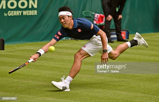 Kei Nishikori of Japan plays a forehand in his match against Lucas Pouille of France during day one of the Gerry Weber Open at Gerry Weber Stadium on...
