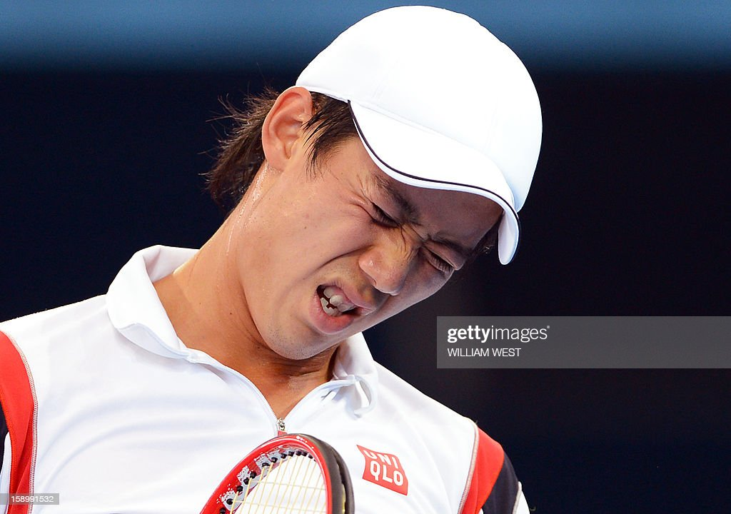 Kei Nishikori of Japan reacts before retiring injured from his semi-final match against Andy Murray of Britain at the Brisbane International tennis tournament on January 5, 2013. AFP PHOTO/William WEST USE