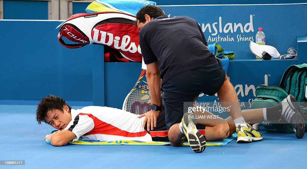 Kei Nishikori of Japan receives treatment before retiring injured in his semi-final match against Andy Murray of Britain at the Brisbane International tennis tournament on January 5, 2013. AFP PHOTO/William WEST USE