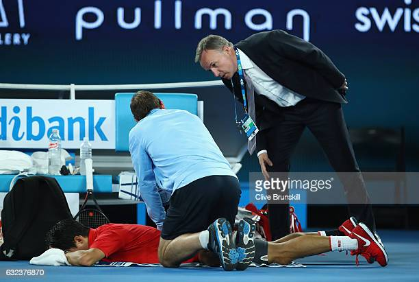 Kei Nishikori of Japan receives treatment from the physio during an injury time out in his fourth round match against Roger Federer of Switzerland on...