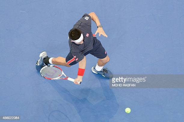 Kei Nishikori of Japan returns a shot against Rajeev Ram of the US in the men's singles second round at the ATP Malaysia Open tennis tournament in...