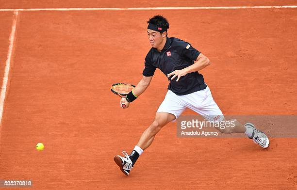 Kei Nishikori of Japan returns to Richard Gasquet of France during the men's single fourth round match at the French Open tennis tournament at Roland...