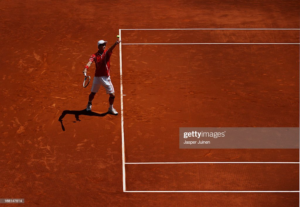 Kei Nishikori of Japan serves the ball to Jurgen Melzer of Austria during day three of the Mutua Madrid Open tennis tournament at the Caja Magica on May 6, 2013 in Madrid, Spain.