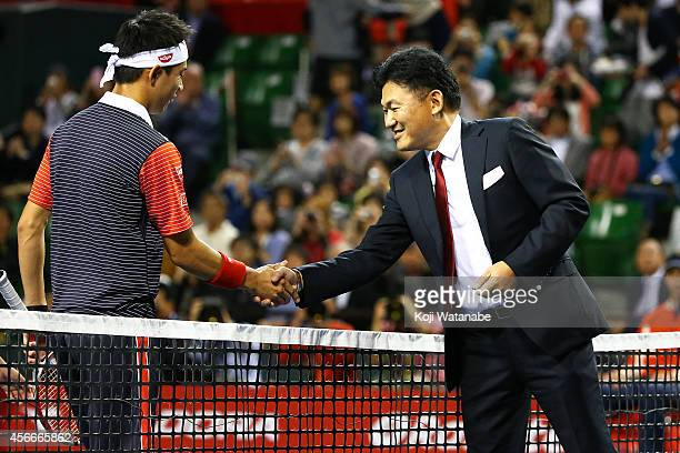 Kei Nishikori of Japan shakes hands with Hiroshi Mikitani chairman and chief executive officer of Rakuten Inc before the men's singles final match...