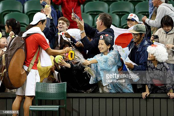 Kei Nishikori of Japan signs his autograph for fans after winning his third round Men's Singles Tennis match against David Ferrer of Spain on Day 5...