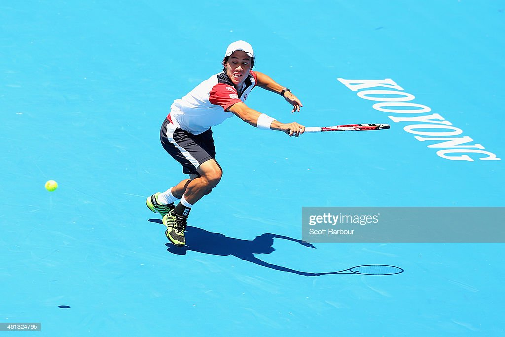 Kei Nishikori of Japan stretches for the ball during his match against Grigor Dimitrov of Bulgaria during day one of the 2014 AAMI Classic at Kooyong...