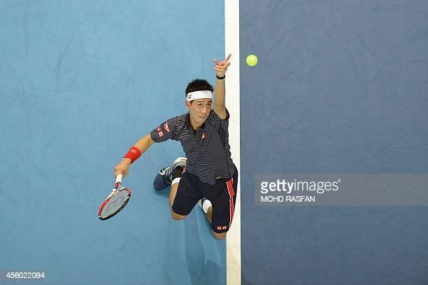 Kei Nishikori of Japan tosses the ball to serve against Rajeev Ram of the US in the men's singles second round at the ATP Malaysia Open tennis...