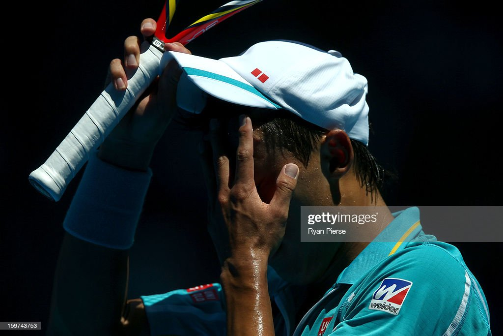 Kei Nishikori of Japan wipes sweat from his face in his fourth round match against David Ferrer of of Spain during day seven of the 2013 Australian Open at Melbourne Park on January 20, 2013 in Melbourne, Australia.