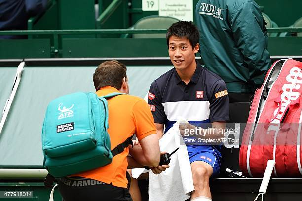Kei Nishikori of Japan with the ATP medical trainer moments before retiring due to injury in his SemiFinal against Andreas Seppi of Italy at the...