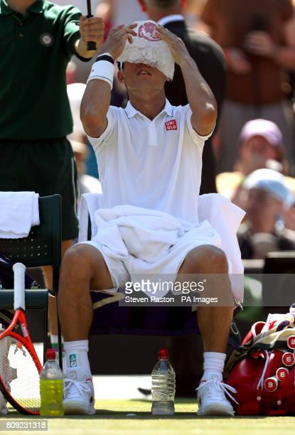 Kei Nishikori uses an ice pack to cool down during his match against Sergiy Stakhovsky on day three of the Wimbledon Championships at The All England...