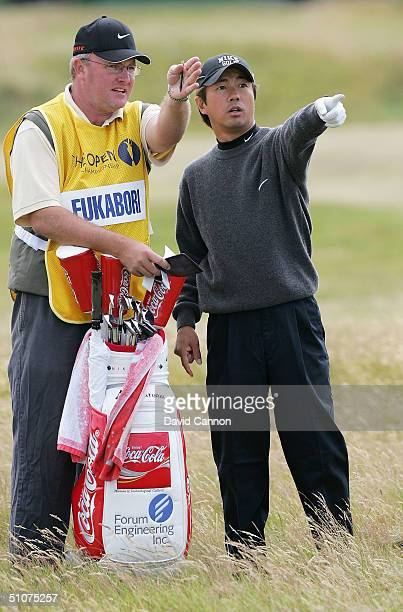 Keiichiro Fukabori of Japan discusses a shot with his caddy on the 16th hole during the second round of the 133rd Open Championship at the Royal...