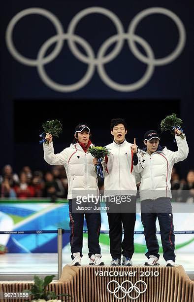 Keiichiro Nagashima of Japan celebrates winning silver Mo TaeBum of South Korea gold and Joji Kato of Japan bronze during the flower ceremony for the...