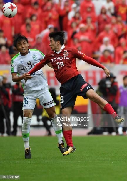 Keiji Tamada of Nagoya Grampus and Takuya Okamoto of Shonan Bellmare compete for the ball during the JLeague J2 match between Nagoya Grampus and...