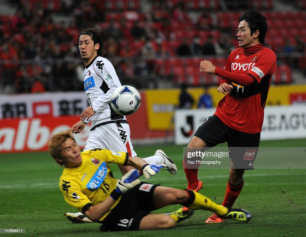 Keiji Tamada of Nagoya Grampus battles for the ball with Lee Ho Seung of Consadole Sapporo during the J.League match between Nagoya Grampus and Consadole Sapporo at Toyota Stadium on April 14, 2012 in Toyota, Japan.