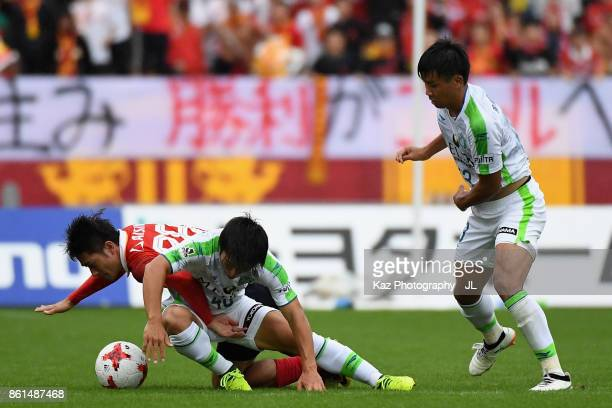 Keiji Tamada of Nagoya Grampus competes for the ball against Temma Matsuda and Miki Yamane of Shonan Bellmare during the JLeague J2 match between...