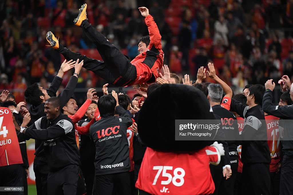 Keiji Tamada of Nagoya Grampus is lifted by his team mates as he leaves the team during the J.League match between Nagoya Grampus and Omiya Ardija at Toyota Stadium on November 29, 2014 in Toyota, Aichi, Japan.